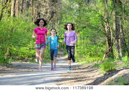 Family sport, happy active mother and kids jogging outdoors, running in forest