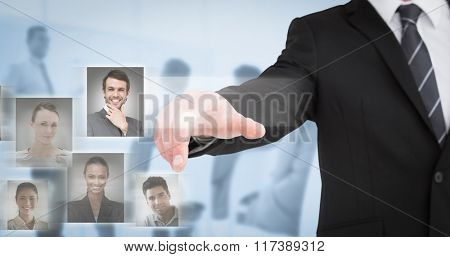 Businessman in suit pointing his finger against blue background