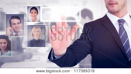 Focused businessman pointing with his finger against grey background