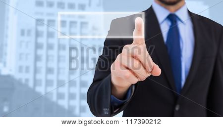 Businessman pointing his finger at camera against low angle view of city buildings