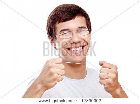 Close up of young hispanic man wearing glasses holding dental floss near his toothy smile with perfect healthy white teeth isolated on white background - dental care and hygiene concept