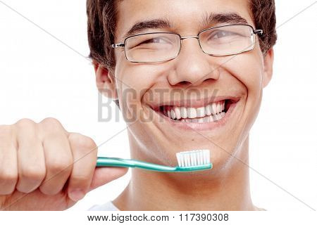 Face close up of young hispanic man wearing glasses holding toothbrush near his toothy smile with perfect healthy white teeth isolated on white background - dental care and hygiene concept
