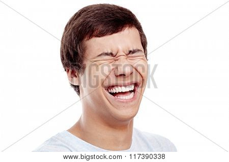 Close up of young hispanic man laughing out loud with closed eyes - laughter is best medicine concept