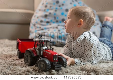 little boy playing at home with tractor