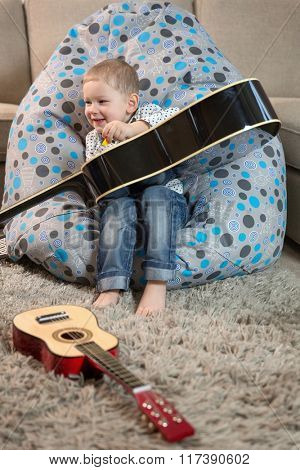 Little happy boy plays the guitar hits, sitting at home on the floor