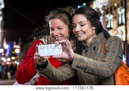 Two women taking selfie with smart phone in night city
