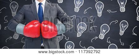 Businessman with boxing gloves against blackboard