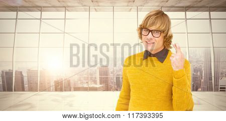 Portrait of hipster crossing his fingers against modern room overlooking city