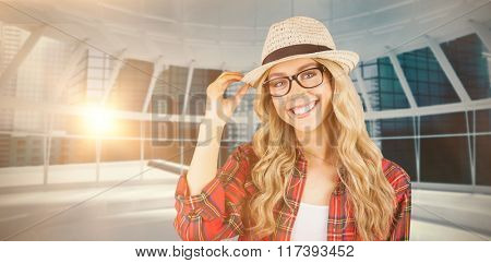 Gorgeous smiling blonde hipster posing against modern room overlooking city