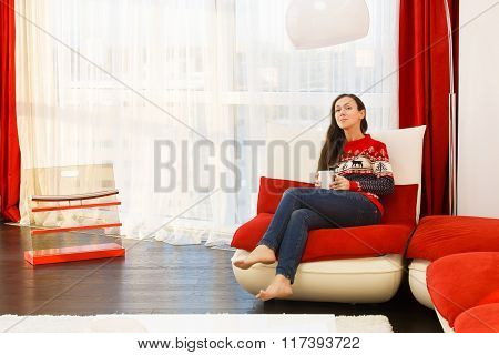Young Woman In Modern Interior Living Room Drinks Coffee At Red Sofa