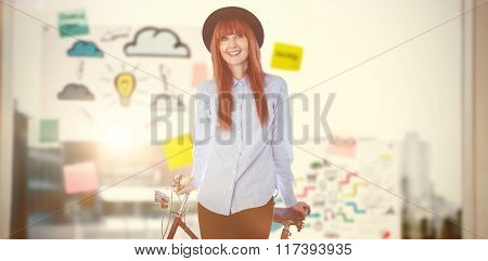 Smiling hipster woman leaning on a bike against adhesive notes on window