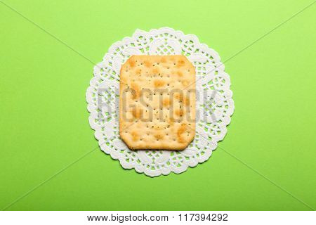One Crispy Cracker With Napkin On Green Background, Close Up