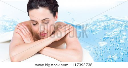Smiling brunette relaxing on massage table against close up on blue sparkling water
