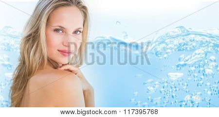 Close up on blue sparkling water against pretty blonde sitting on massage table