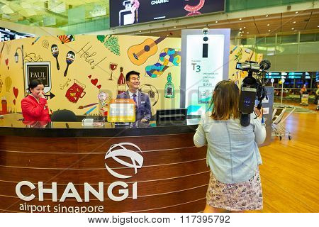 SINGAPORE - NOVEMBER 03, 2015: woman with camera near information desk in Changi Airport. Singapore Changi Airport, is the primary civilian airport for Singapore