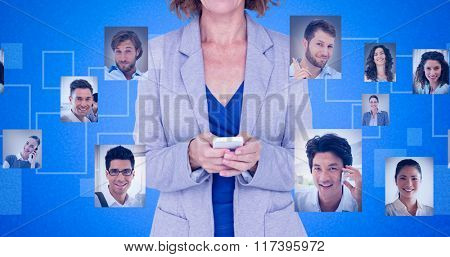 Portrait of smiling businesswoman using mobile phone against blue background