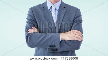 Midsection of businessman standing arms crossed against blue background