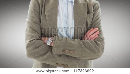 Happy businesswoman standing arms crossed against grey vignette