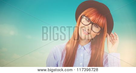 Smiling hipster woman posing face to the camera against blue green background