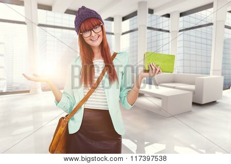 Smiling hipster woman with bag and book against modern room overlooking city