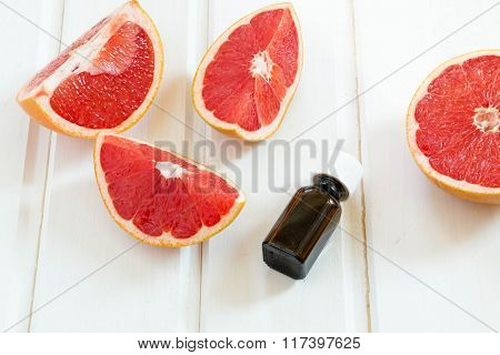 Essential Oil In Glass Bottle With Fresh, Juicy Grapefruit. Spa Concept.