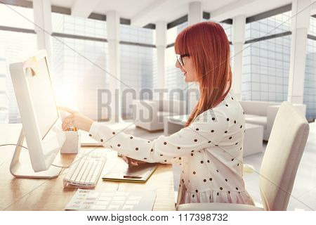 Smiling hipster woman using graphics tablet and pointing screen against modern room overlooking city