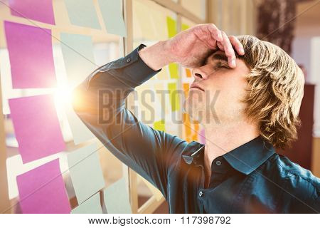 Troubled hipster businessman holding his head against colorful adhesive notes