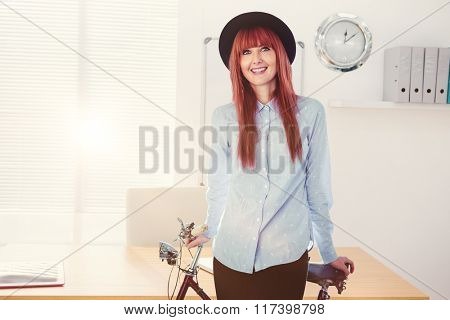 Smiling hipster woman leaning on a bike against a empty office with a laptop