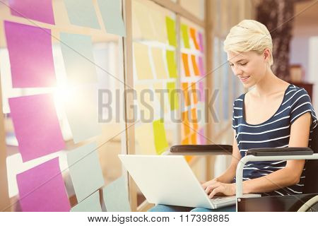 Woman in wheelchair using computer against colorful adhesive notes