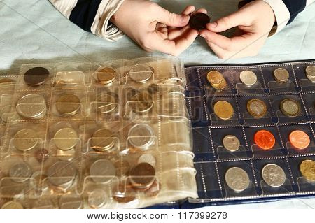 coin album numismatic collection from different countries and ages with human kid hands
