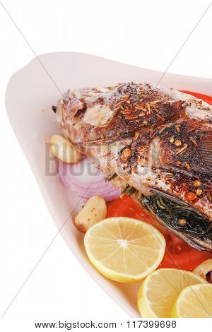 served main course: whole fried seabass served on plate with lemons,tomatoes and peppers . shallow dof