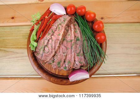 beef slices on wooden plate with peppers on wood