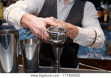 Bartender is squeezing citrus juice in jigger