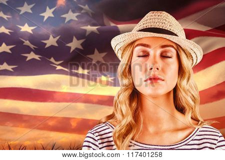 Gorgeous blonde hipster with straw hat against digitally generated american flag rippling over grass
