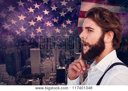 Thoughtful hipster with finger on chin against composite image of colourful fireworks exploding on black background