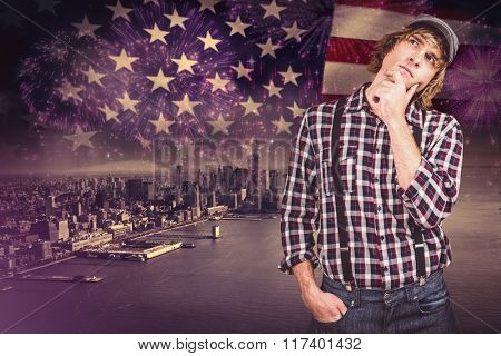 Focused hipster man thinking against composite image of colourful fireworks exploding on black background