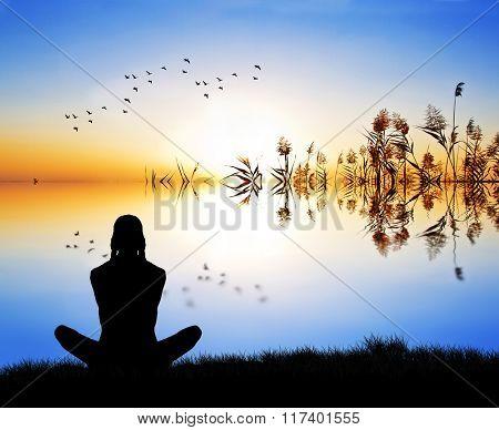 woman meditating waterfront