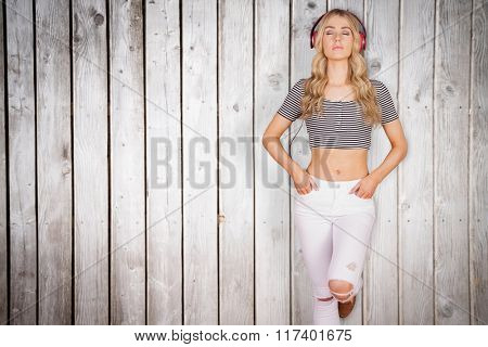 Pretty young woman with headphones against wooden planks