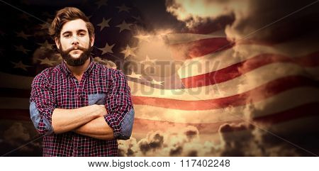 Confident hipster with arms crossed against composite image of digitally generated american flag rippling