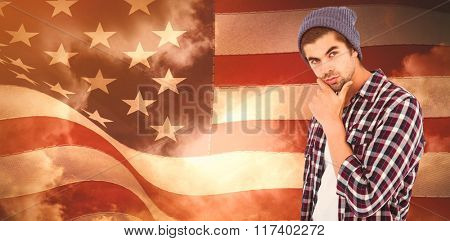 Thoughtful man against white background against composite image of digitally generated united states national flag