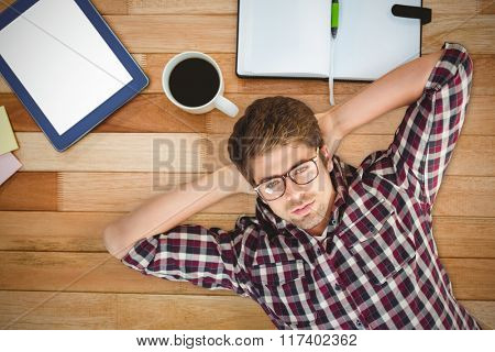 Hipster wearing eye glasses lying on hardwood floor against business desk with tablet and coffee