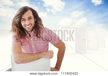 Portrait of hipster smiling while sitting on chair against opening door in sky