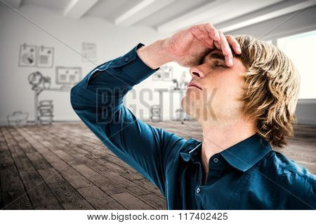 Troubled hipster businessman holding his head against doodle office in hallway