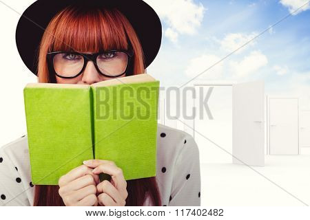 Hipster woman behind a green book against opening door in sky
