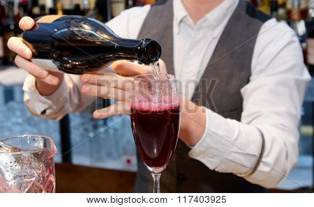 Bartender is pouring sparkling wine in the glass, making shrub cocktail