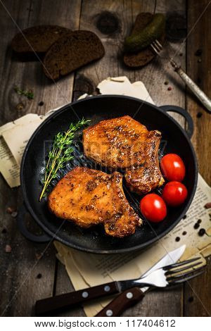 Grilled pork chop. Grilled meat on skillet