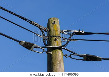 wooden electricity post against blue sky