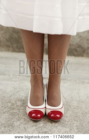 Women's legs in beige delicate tights with retro shoes, vintage filter applied