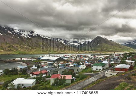 Mighty fjords with mountains covered by snow rise above the town of Olafsfjordur, Northern Iceland
