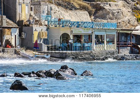 Traditional Greek tavern with tourists at rocky coastline